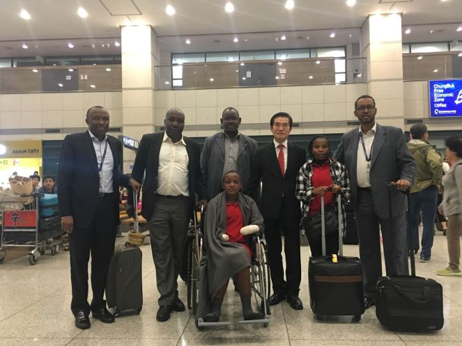 On September 27th 2016, Mwende's Arrival at Incheon International Airport, From Left Deputy Head of Mission Gathoga Chege, Jackline Mwende on wheel chair accompanied by Hellen Kanini Nurse Machakos County Hospital, in LG shirts Dr. Lee Seung Ho CEO Korea Prosthetics Laboratory in red tie Amb Mohamed Gello at the far right among Kenya community in Korea receive Mwende at Incheon International Airport, Korea